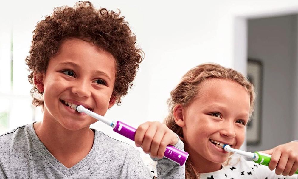due bambini usano lo spazzolino elettrico